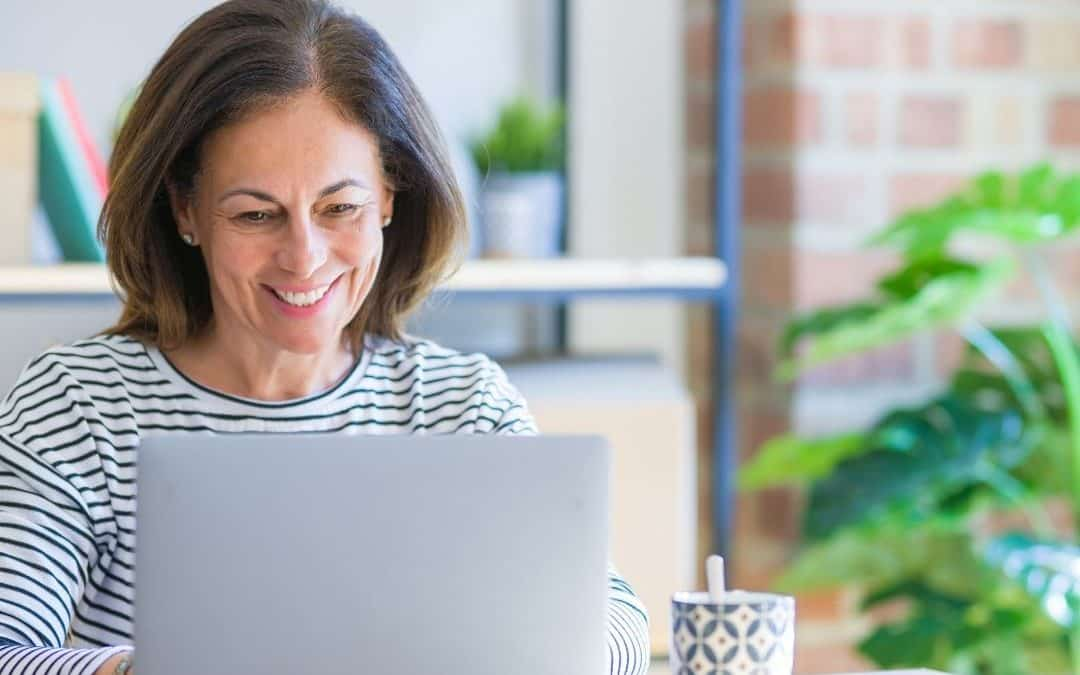Woman at computer working to get clients online. She is smiling because she has found her ideal clients after listening to A Profitable Impact.