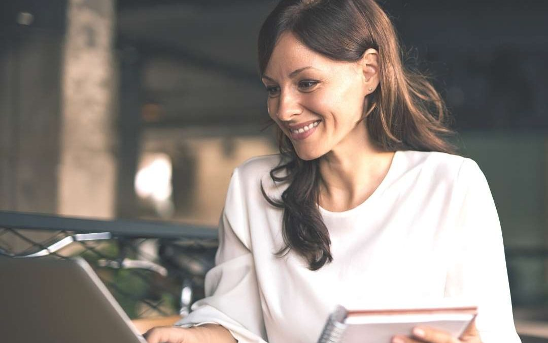 Woman smiling as she works from her computer. She's happy because she's able to charge what she is worth on a sales call.