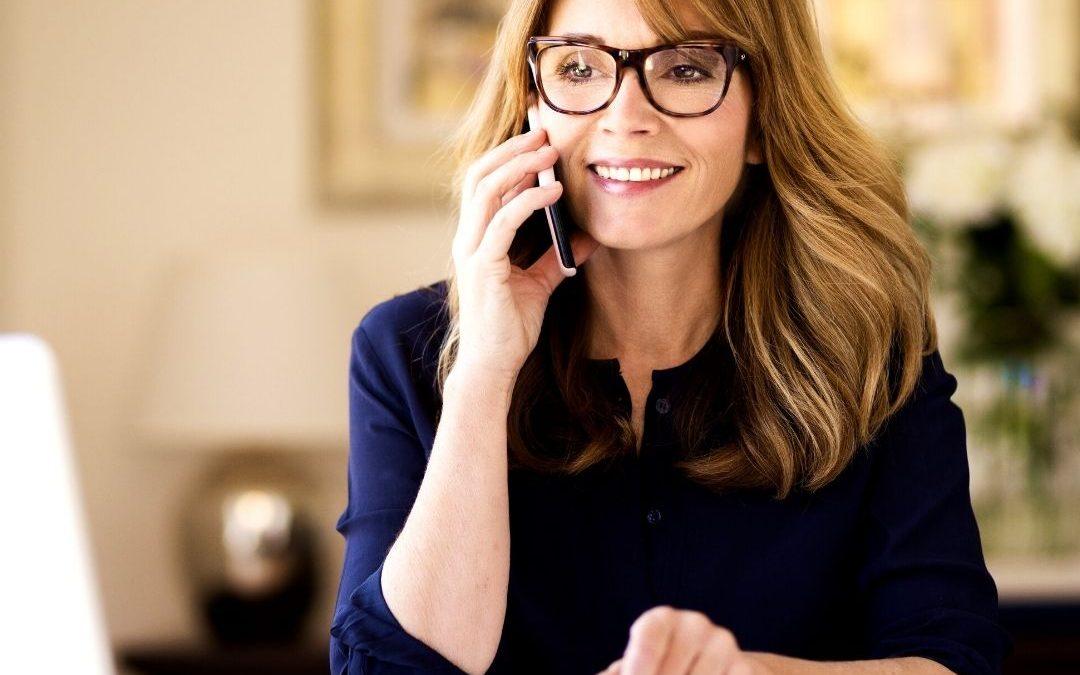 Woman on phone having a sales conversation.